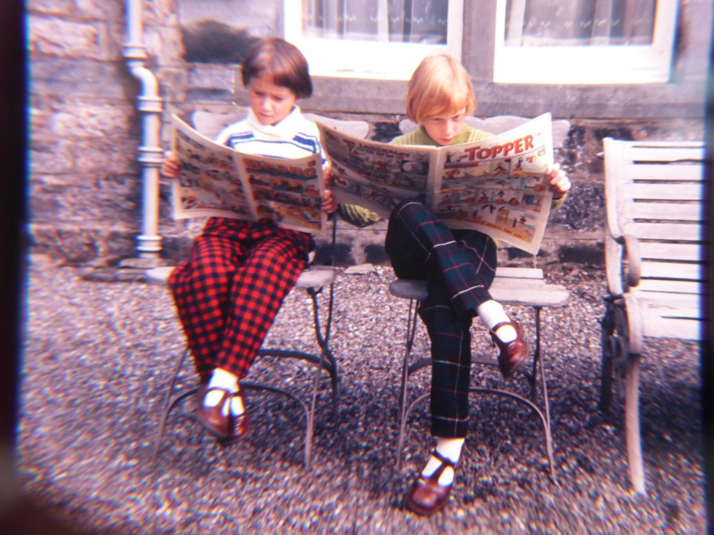 girls in check trousers reading comics