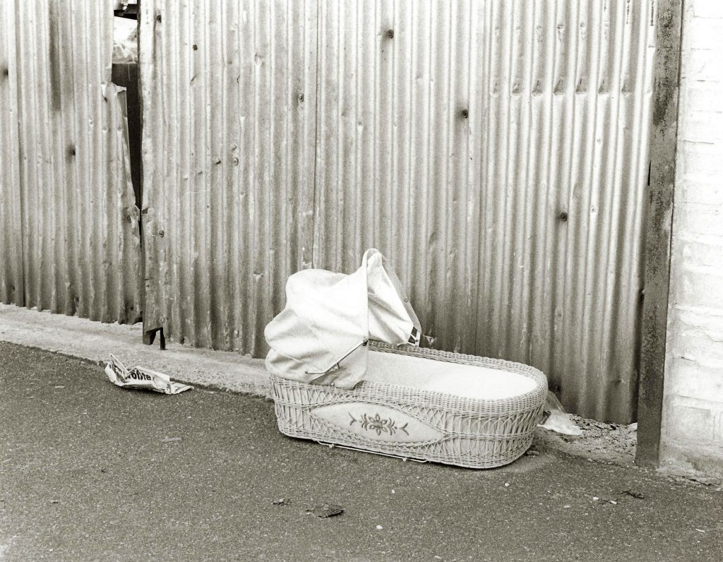baby cot abandoned by corrugated fence