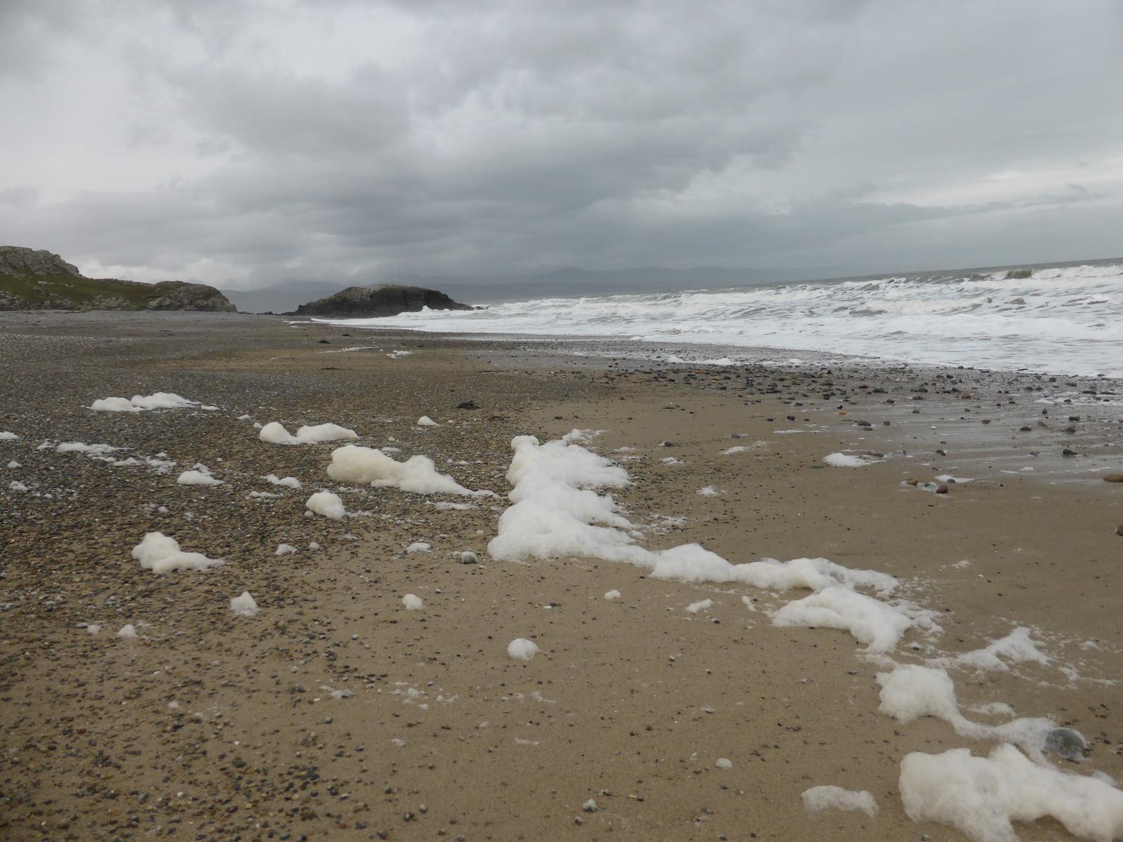 foam and shingle on the beach